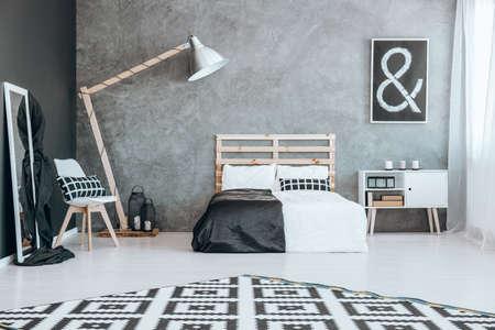 Zwart en wit tapijt met patroon in een stijlvolle kamer met bed