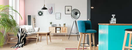 dining table and chairs: Teal bar stools in a living room standing behind a black wall in an interior housing modern furniture like a stylish sofa or a coffee table