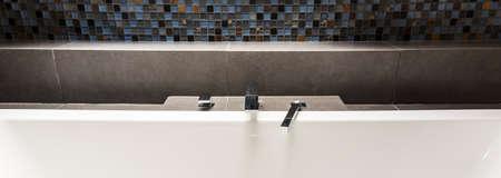 Panoramic close-up of chrome modern washbasin faucet idea