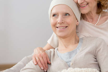 fighting cancer: Happy cancer survivor with a headscarf, lying in an embrace of a close relative Stock Photo