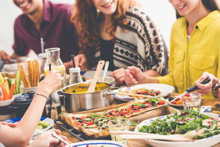 Vegan party, young friends trying new vegan recipes together, chatting and having fun at communal table full of colorful sumptuous dishes Stock Photo