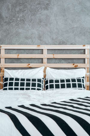 Close-up photo of black and white striped blanket on the bed with cushions