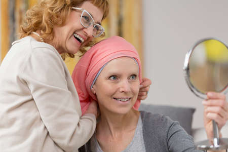 Woman after chemotherapy receiving a new, red scarf from a friend, and trying it on while looking into the small mirror