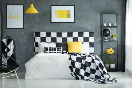 Black And White Checkered Bedsheets And Yellow Pillow On Bed In Bedroom  With Metal Shelf Stock