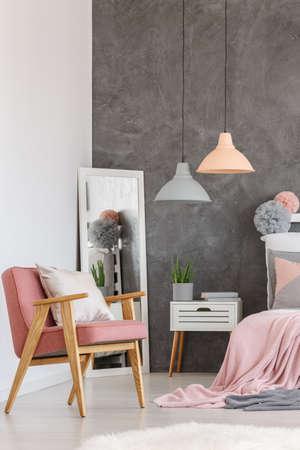 居心地の良いベッドルーム キングサイズ ベッド、デザイン ランプとミラーのピンクの寝具で枕で白いビンテージ ピンク椅子