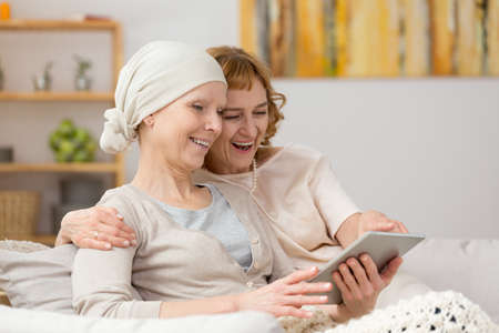 fighting cancer: Two women sitting on a sofa enjoying their time laughing, while looking at a tablet screen Stock Photo