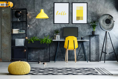 Yellow braided pouf on black and white carpet in dark work area with lamp and yellow chair