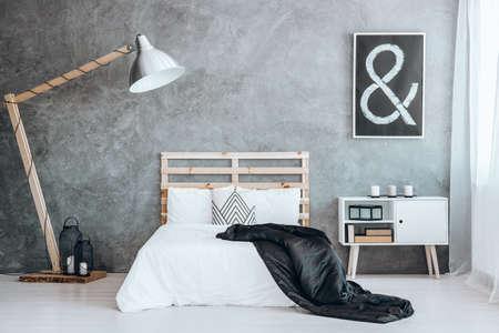 木製ベッドに配置されて幾何学的なパターンを持つ小さな装飾クッション