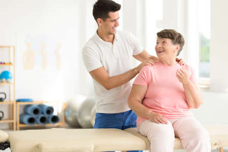 Physiotherapist performing a rehabilitation session with his senior ward