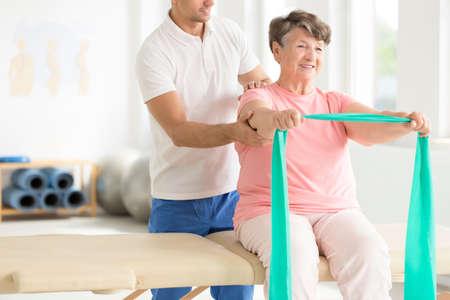Starsza kobieta robi aktywne ćwiczenia pnf z szalikami w kolorze turkusowym jako część programu rehabilitacji z fizjoterapeutą
