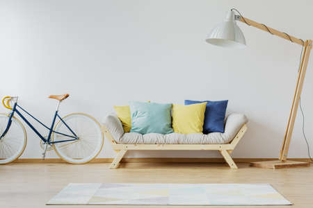 Colorful pillows on couch in modern scandinavian flat with wooden couch, lamp, rug, vintage bike and white wall Zdjęcie Seryjne