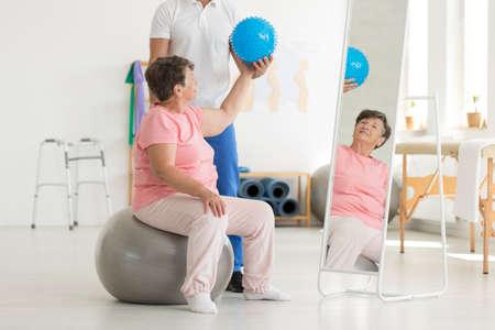 Set van isometrische evenwichtsoefeningen met inbegrip van verrijkt blauwe bal gehouden door de senior patiënt terwijl ze zit op een grijze fit bal voor een spiegel