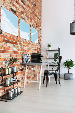 Wooden desk with handmade wine rack standing in living room with brick wall