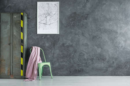 Mint chair with pink coverlet standing next to grey old locker in a room with empty wall