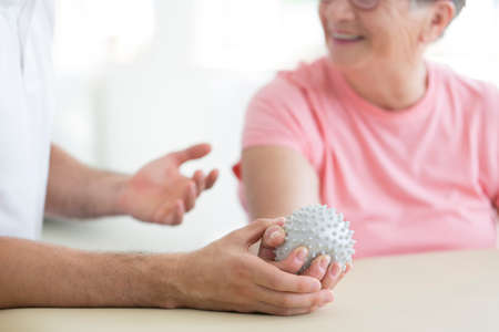 Paciente de un asilo de ancianos haciendo ejercicios activos de pnf con una pelota de púas gris utilizada con fines de rehabilitación Foto de archivo - 87560733