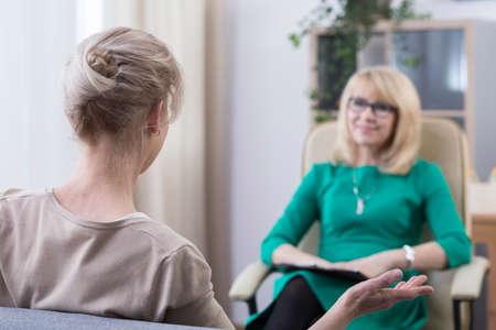 친절한 우아한 중간 세 심리 치료사는 그녀의 일상적인 문제에 대해 이야기하는 여성 환자의 이야기를 듣고 사무실에 앉아