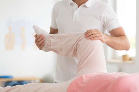 Terapista che allevia il dolore nell'area del ginocchio del paziente attraverso la fisioterapia Archivio Fotografico - 87560741