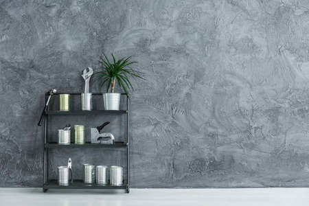 Copy space photo of small black metal rack with handymans supplies and potted plant