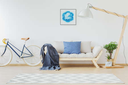 Bright nordic room interior with light blue and white design, wooden couch, oversize lamp, bike and mock-up poster