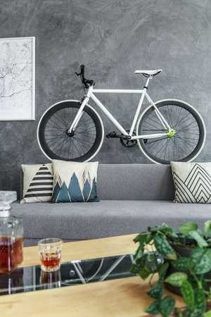 Sports bike standing on the back of grey sofa in dark industrial apartment