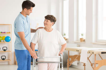 Elderly ward using a walking frame to support herself during physiotherapy Stock Photo