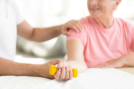 Senior patient committed to an active, isometric exercise session with her physiotherapist at nursing home Stock Photo