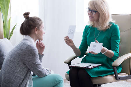 Friendly female psychologist showing a drawing of family house to young girl with mental problem
