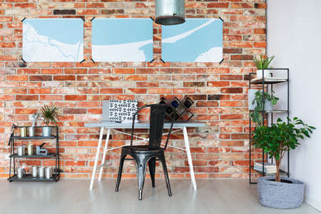 Three posters of map hanging on brick wall above wooden desk with wine rack