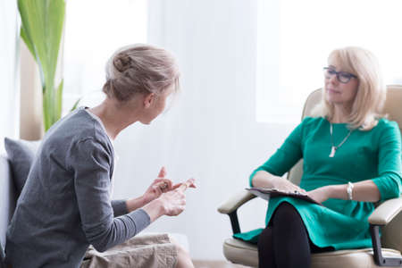 Female patient talking about her worries with therapist in the office, psychotherapy and mental health concept