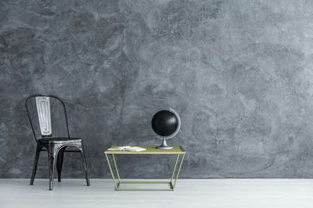 Black globe standing on small table by the copper chair in room with empty wall