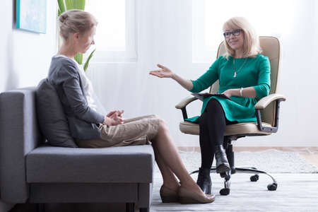 Divorce counseling and post-divorce therapy concept, mature divorced woman getting mental health support from friendly female psychiatrist, sitting in bright office on sofa
