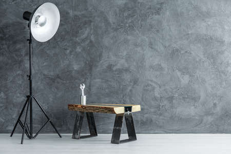 Room with empty wall and adjustable wrench placed in a metal can standing on handmade table