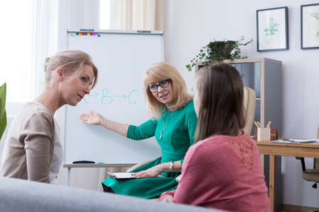 Worried mother and young introverted daughter visiting child psychologist, therapist helping teenage girl to overcome shyness Stock Photo