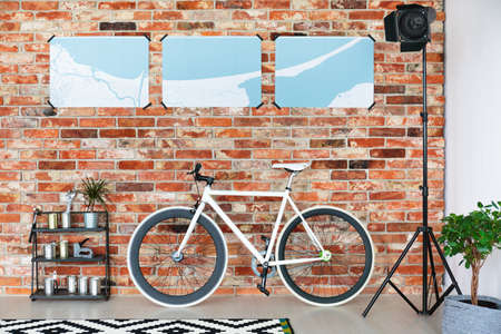 White bike standing against brick wall in room with studio lamp and map Stock Photo
