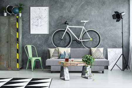 Black and white bicycle placed on back of the couch in dark industrial room