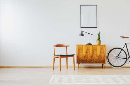 흰색 벽과 빈티지 액세서리, 의자, 램프, 나무 찬장, 깔개 및 복고풍 자전거가있는 현대적인 밝은 실내 장식의 오래된 가구 스톡 콘텐츠 - 87560770