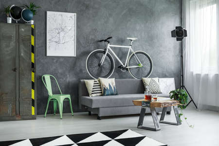 Grey sofa with decorative cushions with pattern and sports bike on the back in industrial living room