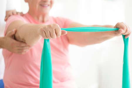 Mujer Senior sosteniendo una bufanda verde azulado en sus manos mientras realiza ejercicio de rehabilitación pnf activo con la ayuda de su terapeuta Foto de archivo - 87560775