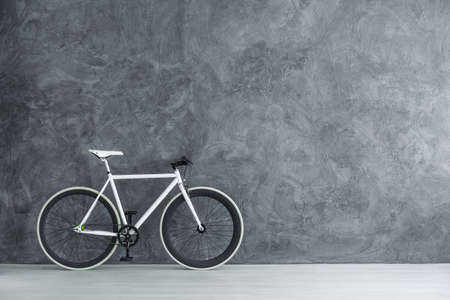 Photo with copy space of white bike standing in a room with raw grey wall