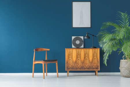 Stylowe wnętrze mieszkania z niebieską ścianą w stylu vintage z drewnianą szafką, krzesłem, makietą i tropikalną rośliną doniczkową