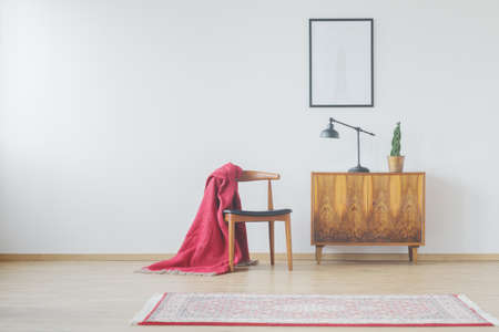 Modern room with vintage accessories, wooden cupboard, old-fashioned rug, retro chair, red blanket and poster mock-up