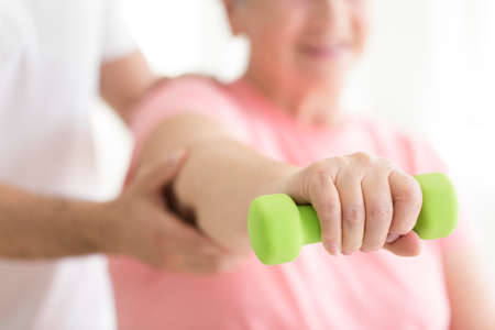 Elderly patient holding a minor dumb-bell in her right hand during isometric physiotherapy Stockfoto
