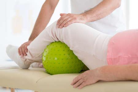 Paciente mayor que se somete a rehabilitación en un hospital con una pelota de masaje verde debajo de su pierna izquierda