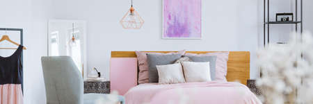 Pink decorative board with tacks standing by a bed with pillows and wooden bedhead