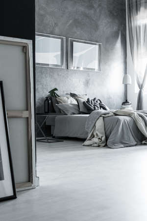schemes: Bedroom in monochromatic color scheme with posters on dark textured wall and grey quilt on bed
