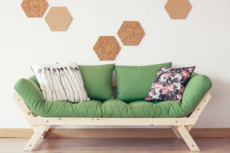 Floral patterned pillow on green wooden sofa against white wall with natural cork Stock Photo