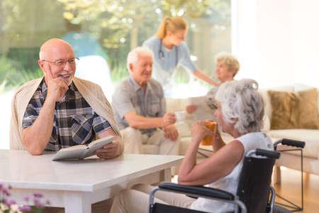 Oudere man met een boek die aan gehandicapte vrouw spreekt die thee drinkt