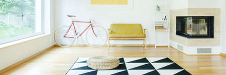 Bright simple living room with fireplace and red and white bike standing next to couch Stock Photo