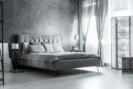 Dark grey bedroom with comfortable king-size bed under window with decorative curtains and screen