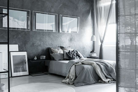 Screen And Posters In Dark Grey Bedroom With Bedsheets On King Size Bed  Against Textured